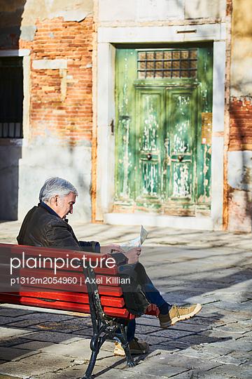 Mann mit Stadtplan auf einer Bank - p1312m2054960 von Axel Killian