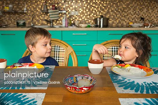 Portrait of boy and his little sister eating breakfast in the kitchen - p300m2043170 by Vladimir Godnik