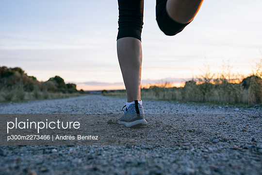 Woman running on country road during sunset - p300m2273466 by Andrés Benitez