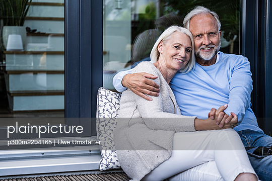 Man holding hand of woman while sitting at balcony - p300m2294165 by Uwe Umstätter