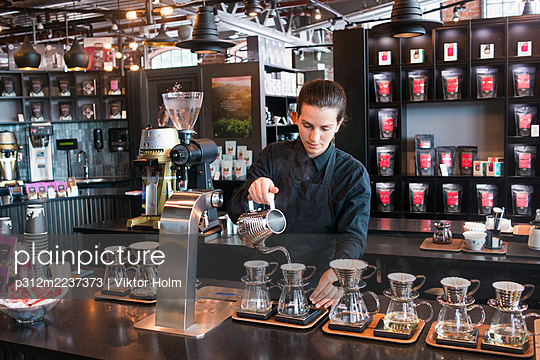 Female barista preparing coffee at counter - p312m2237373 by Viktor Holm