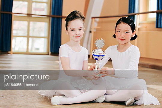 two young ballet dancers holding trophy