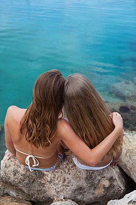 Freundinnen schauen Arm in Arm auf Wasser - p045m2053134 von Jasmin Sander