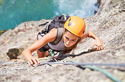 Focused, determined female rock climber scaling rock - p1023m1561186 by Trevor Adeline