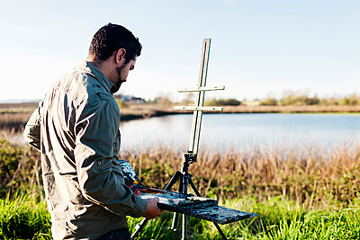 Side view of painter adjusting paint tray on easel at field - p1166m1473621 by Cavan Images