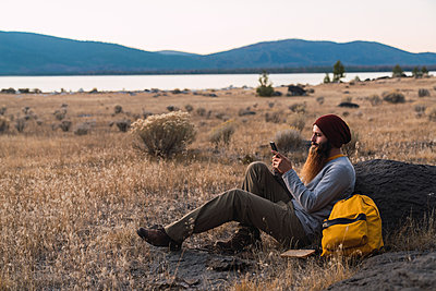 USA, North California, bearded young man using cell phone during a break on a hiking trip near Lassen Volcanic National Park - p300m2059128 by Kike Arnaiz