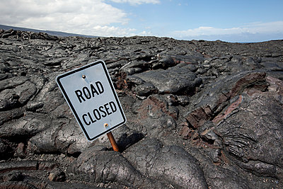 Road closed sign partially covered in hardened pahoehoe lava from recent flows, Hawaii Volcanoes National Park; Island of Hawaii, Hawaii, United States of America - p442m936884f by Charmian Vistaunet photography