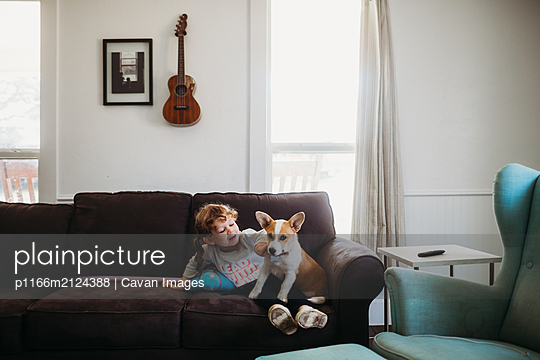 Young girl playing with corgi puppy on couch in living room - p1166m2124388 by Cavan Images