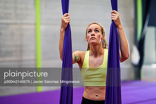 Young woman preparing for aerial silk in an exercise room - p300m2140679 by Javier Sánchez Mingorance
