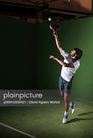 Male athlete servicing ball while playing padel tennis in sports court at night - p300m2250421 by David Agüero Muñoz