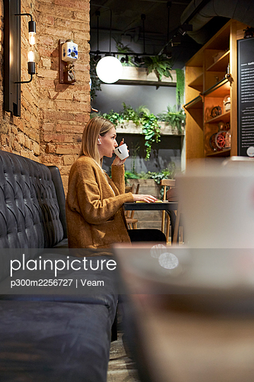 Beautiful woman having cup of coffee at cafeteria - p300m2256727 by Veam