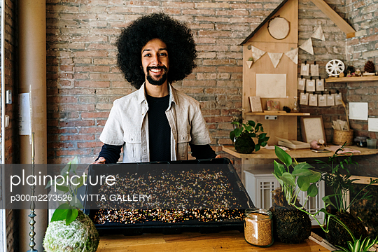 Male gardener showing variety of seeds in plastic tray - p300m2273526 by VITTA GALLERY