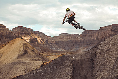 Rear view of young male jumping with mountain bike in desert landscape - p1166m2162916 by Cavan Images