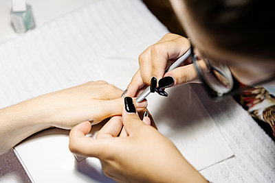 Top view of crop stylist removing cuticle from fingers of woman - p1166m2216684 by Cavan Images