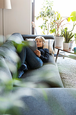 Mature woman relaxing on couch at home using tablet - p300m2144806 by Valentina Barreto