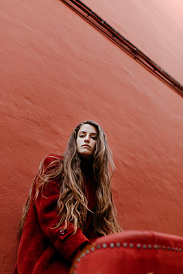Portrait of young woman with long brown hair against red wall - p300m2160711 by Tania Cervián