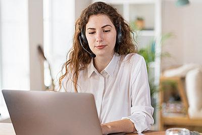 Beautiful female customer service representative using laptop at home office - p300m2276469 by Steve Brookland