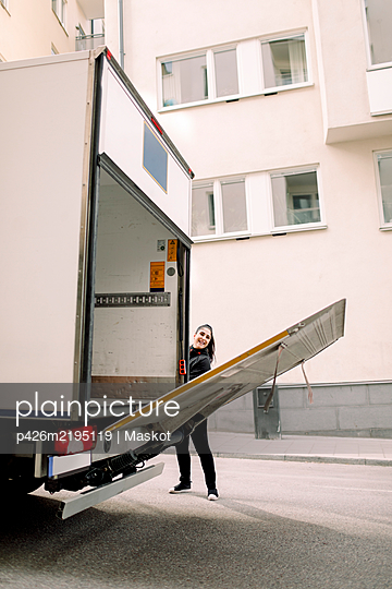 Young delivery woman with truck on street in city - p426m2195119 by Maskot
