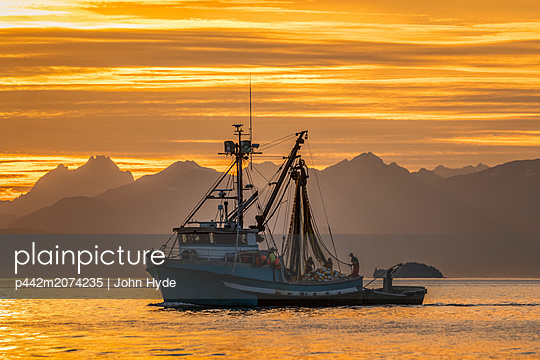 Seiner anchored in Amalga Harbor at sunset awaiting a commercial salmon opening, near Juneau, Southeast Alaska; Alaska, United States of America - p442m2074235 by John Hyde
