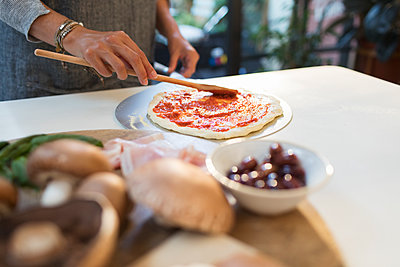 Woman spreading tomato sauce on pizza dough in kitchen - p1023m2208343 by Sam Edwards