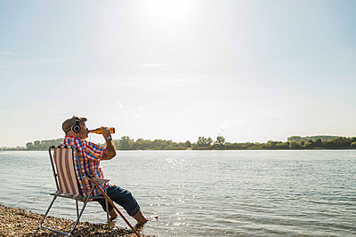 Germany, Ludwigshafen, senior man with headphones sitting on folding chair at riverside drinking beer - p300m1068855f by Uwe Umstätter