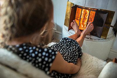 Woman warming feet by fireplace - p312m1131438f by Fredrik Schlyter