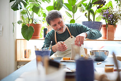 Mature man making craft product in pottery class - p426m2205089 by Maskot