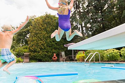 Caucasian children jumping into swimming pool - p555m1421665 by JGI/Jamie Grill