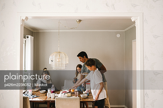 Family at dining table seen through doorway of house - p426m2238052 by Maskot