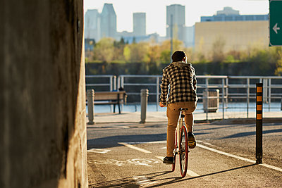 Youthful man on fixed gear bike cycling around city, Montreal, Quebec, Canada - p1362m1553698 by Charles Knox