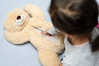 Mädchen schneidet Teddybär auf - p1625m2230304 von Dr. med.