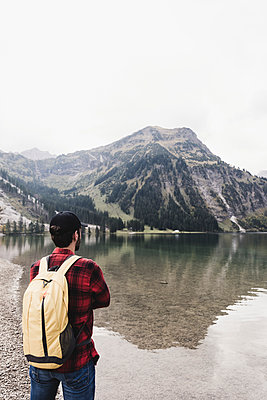 Austria, Tyrol, Alps, hiker standing at mountain lake - p300m1505194 by Uwe Umstätter
