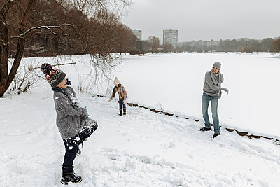 Father and two children having a snowball fight - p300m2166441 by Ekaterina Yakunina