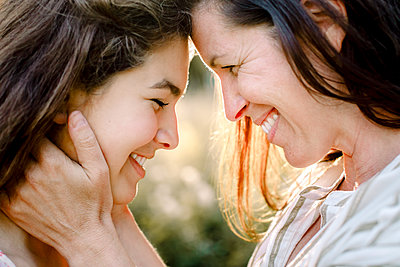 Smiling mother embracing daughter in yard - p426m2227876 by Maskot