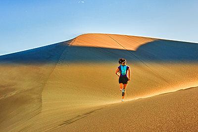 Hispanic woman running on sand dune - p555m1478042 by Michael DeYoung