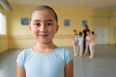 Portrait of smiling girl in ballet studio - p555m1491105 by Mark Edward Atkinson