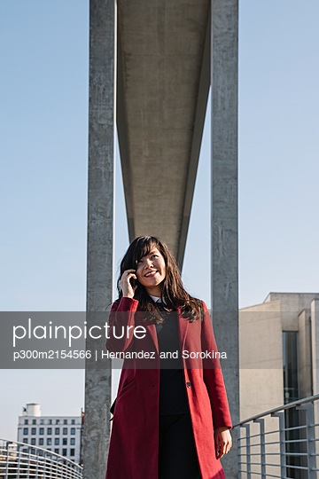 Businesswoman standing near to modern building and using smartphone - p300m2154566 by Hernandez and Sorokina