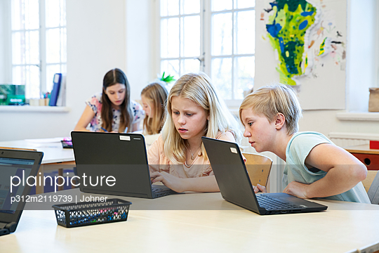 Girls using laptops at school - p312m2119739 by Johner