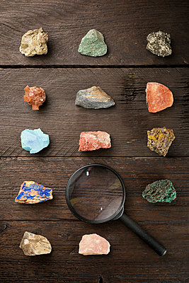 Overhead view of colorful gemstones with magnifying glass on wooden table - p1166m1577406 by Cavan Social