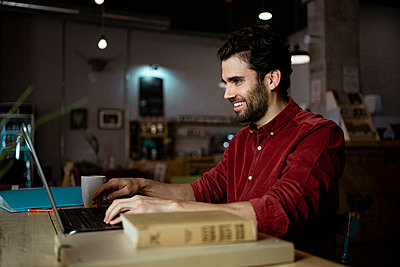 Smiling male entrepreneur working on laptop in illuminated coffee shop - p300m2276355 by Rafa Cortés