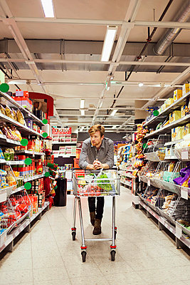 Young man leaning on shopping cart at supermarket aisle - p426m1017979f by Maskot
