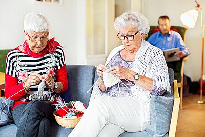 Senior women knitting while man reading book in background at nursing home - p426m977470f by Maskot