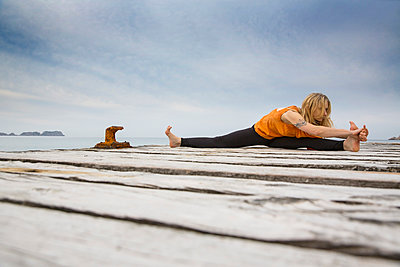 Mid adult woman practicing yoga on wooden sea pier - p429m974451f by RUSS ROHDE