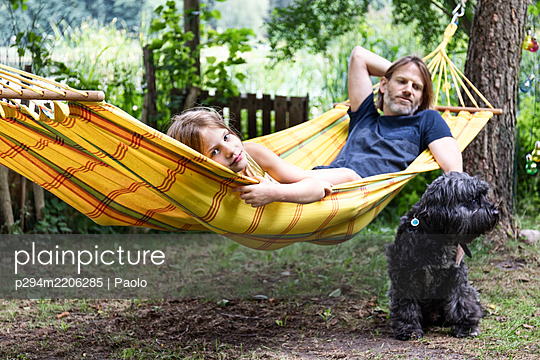 Father and daughter relaxing in a hammock - p294m2206285 by Paolo