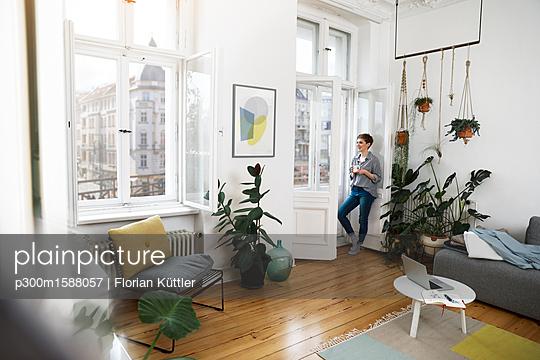 plainpicture - plainpicture p300m1588057 - Relaxed woman standing at t... - plainpicture/Westend61/Florian Küttler