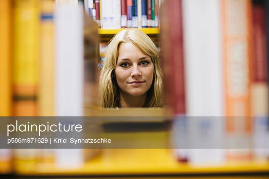 Junge Frau in einer Bibliothek - p586m971629 von Kniel Synnatzschke