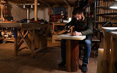 Bearded craftsman making leather handicraft - p1166m2234376 by Cavan Images