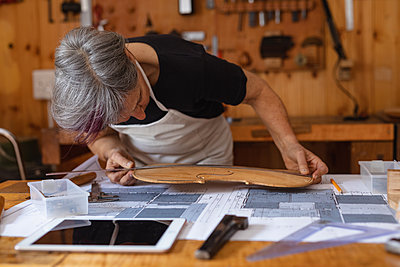Female luthier at work in a workshop - p1315m2131459 by Wavebreak