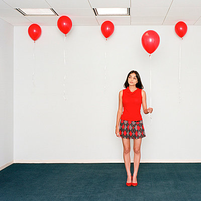 Young woman holding balloon in office - p3721919 by James Godman