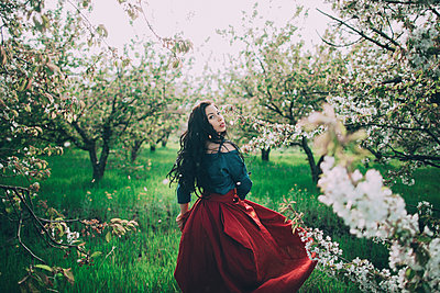 Caucasian woman walking near flowering trees - p555m1491492 by Kateryna Soroka